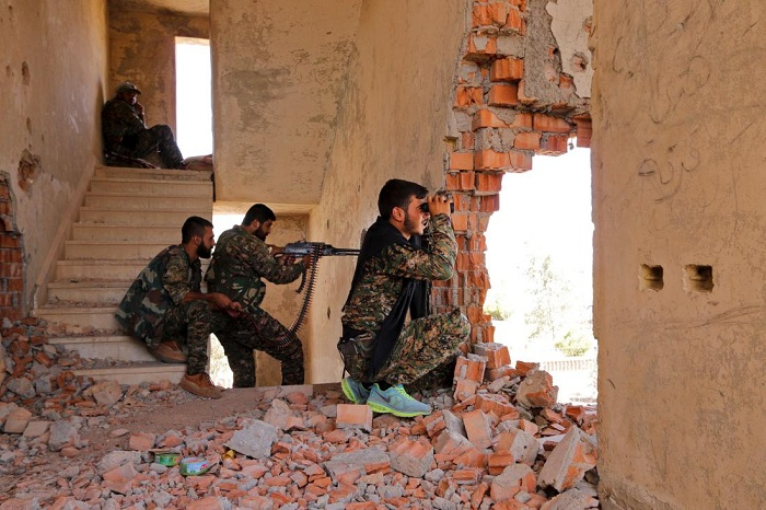 Kurdish People's Protection Units fighters take up positions inside a damaged building in al-Vilat al-Homor, as they monitor the movements of Islamic State fighters who are stationed in Ghwayran