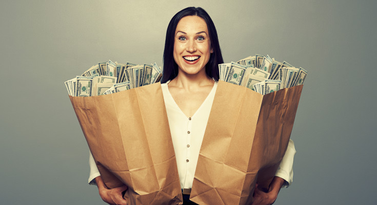 excited businesswoman holding two paper bags with money and smiling. photo in studio over grey background