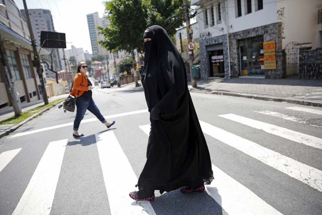 Gisele Marie, a Muslim woman and professional heavy metal musician, crosses a street after a rehearsal at a studio in Sao Paulo