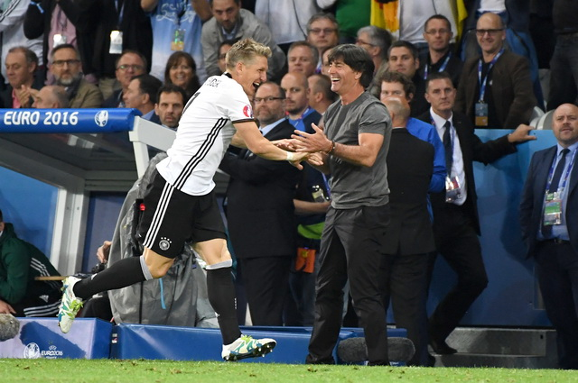 Germany's Bastian Schweinsteiger celebrates with Germany coach Joachim Loew after scoring his side's second goal during the Euro 2016 Group C soccer match between Germany and Ukraine at the Pierre Mauroy stadium in Villeneuve d'Ascq, near Lille, France, Sunday, June 12, 2016. (AP Photo/Geert Vanden Wijngaert)