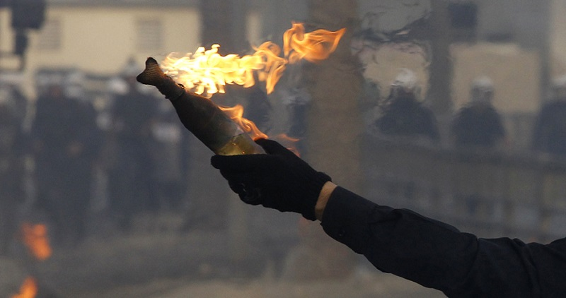 A protester holding a Molotov cocktail walks towards riot police during clashes in Sanabis village