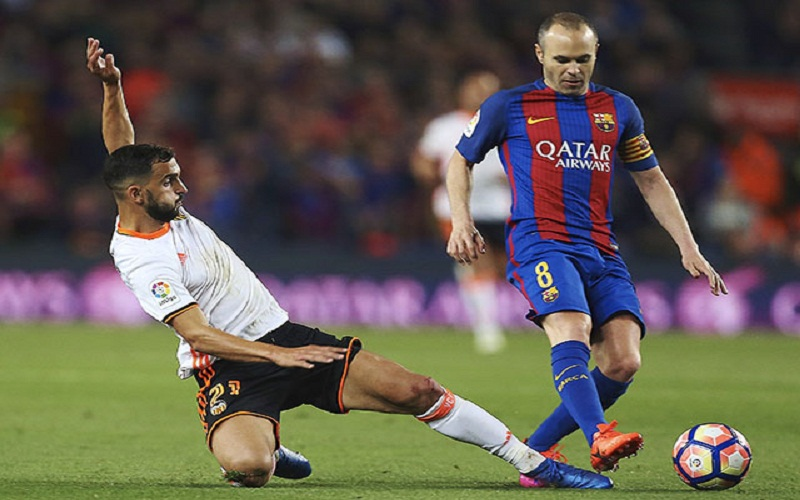 epa05858909 FC Barcelona´s midfielder Andres Iniesta (R) fights for the ball with defender Martin Montoya (L) of Valencia CF during their Spanish First Division soccer match played at Camp Nou stadium in Barcelona, 19 March 2017.  EPA/Alejandro Garcia