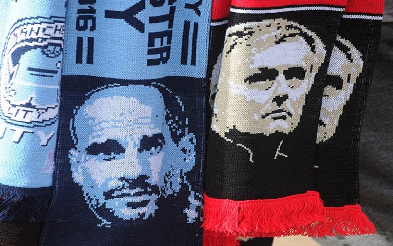 epa05533081 A scarf seller holds up half and half scarves displaying pictures of Manchester United manager Jose Mourinho (R) and Manchester City manager Josep Guardiola (L) outside Old Trafford before the English Premier League soccer match between Manchester United and Manchester City at Old Trafford, Manchester, Britain, 10 September 2016.  EPA/PETER POWELL EDITORIAL USE ONLY. No use with unauthorized audio, video, data, fixture lists, club/league logos or 'live' services. Online in-match use limited to 75 images, no video emulation. No use in betting, games or single club/league/player publications