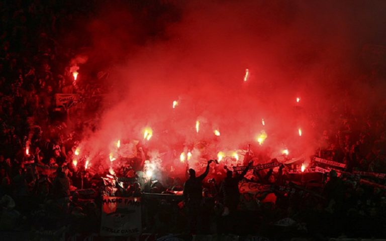 St.-Etienne supporters light flares ahead of the Europa League round of 32 first leg soccer match between Manchester United and St.-Etienne at the Old Trafford stadium in Manchester, England, Thursday, Feb. 16, 2017 . (AP Photo/Dave Thompson)