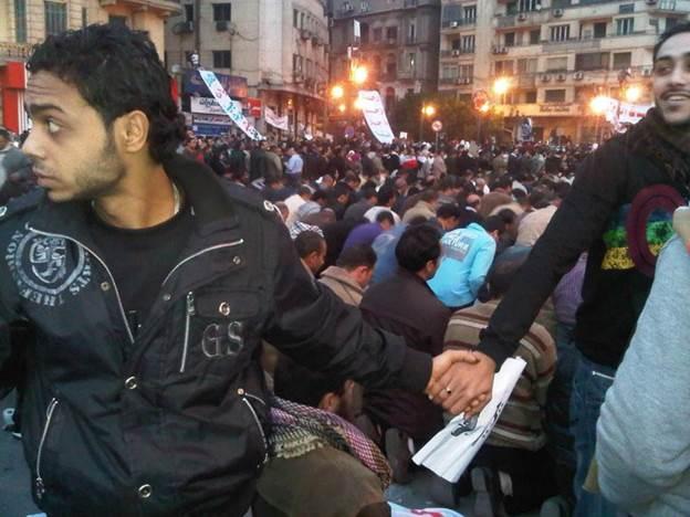 Христијанин ги заштитува муслиманите за време на молитва во Каиро 2011